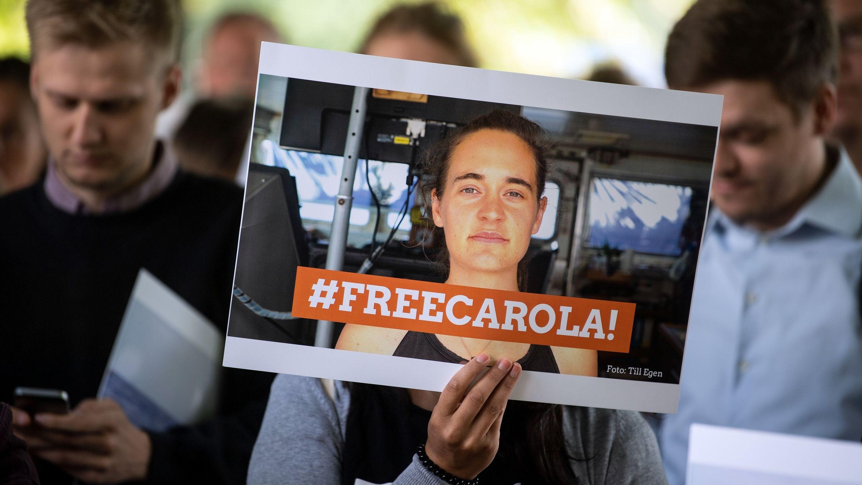 """Eine Demonstrantin in Köln hält ein Bild von der Sea-Watch-Kapitänin Carola Rackete mit der Aufschrift """"#FREECAROLA!"""" in der Hand."""