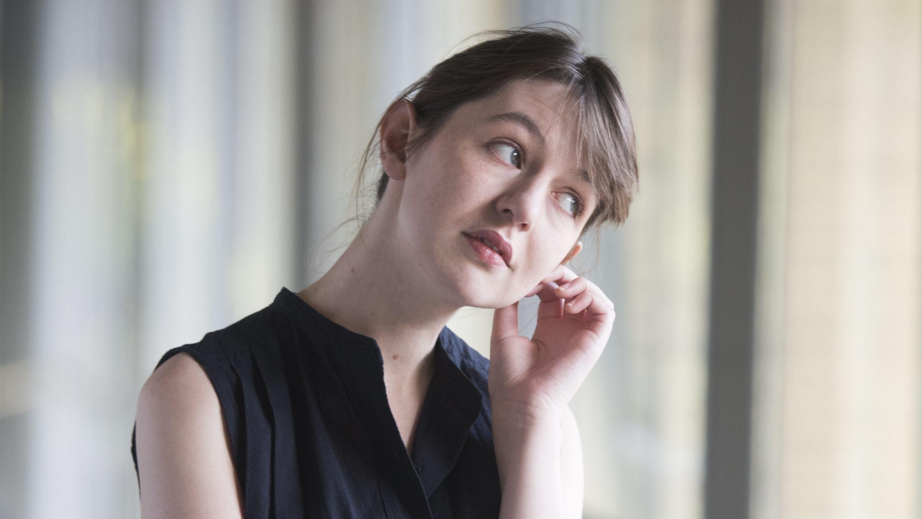 Schriftstellerin Sally Rooney greift sich mit der linken Hand ans Ohr und blickt mit seitlich geneigtem Kopf an der Kamera vorbei