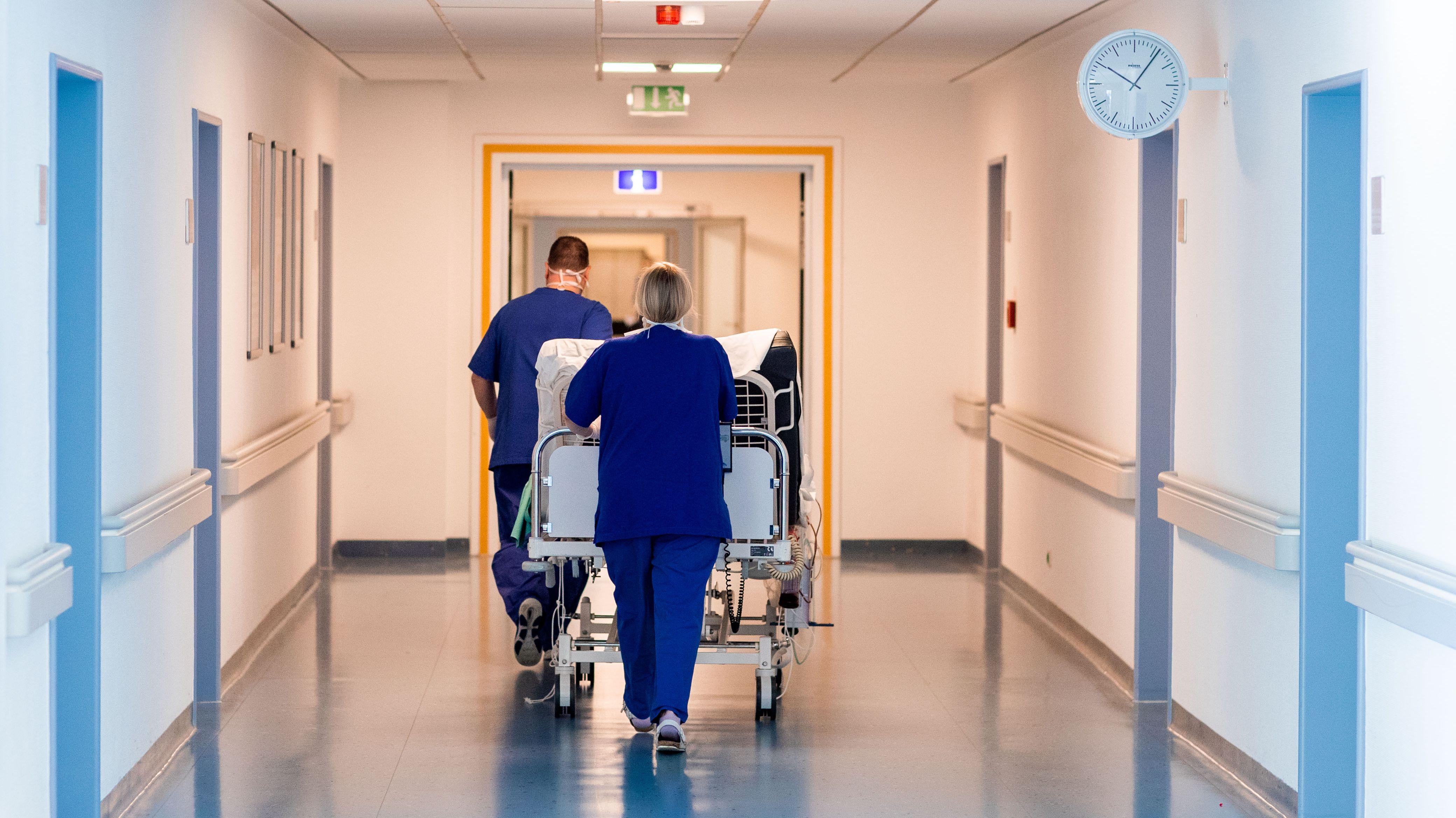 Klinikpersonal schiebt ein Krankenbett