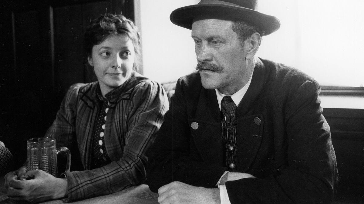 """Schwarzweißszene aus """"Rumplhanni"""": Schauspielerin Monika Baumgartner und Karl Obermayr sitzen in Tracht an einem Tisch"""