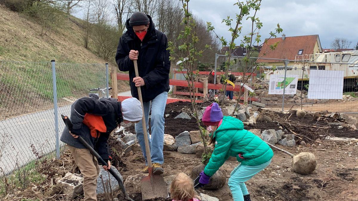 Kinder der Jugendkunstschule in Fürth pflanzen Bäume.