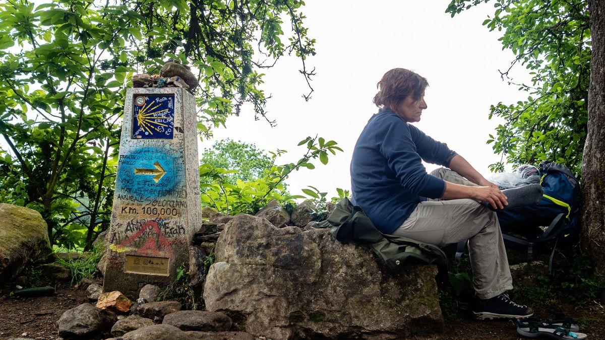 Eine Frau macht Rast beim Meilenstein, von dem aus es noch 100 Kilometer bis Santiago de Compostela sind.