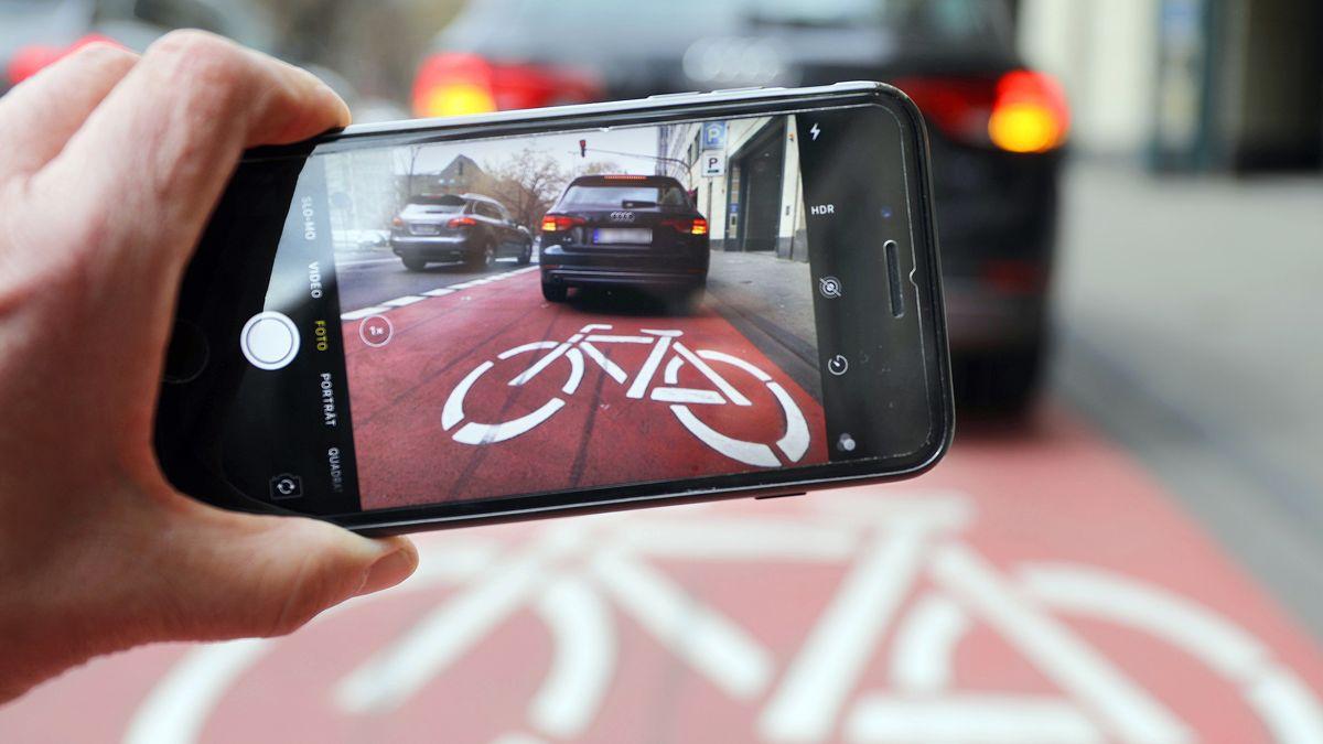 Auf einem Smartphone ist das Bild eines Autos zu sehen, das auf einem Radstreifen hält.