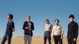 Die fünf männlichen Bandmitglieder von June stehen in einer Düne. | Bild:Niklas Adrian Vindelev
