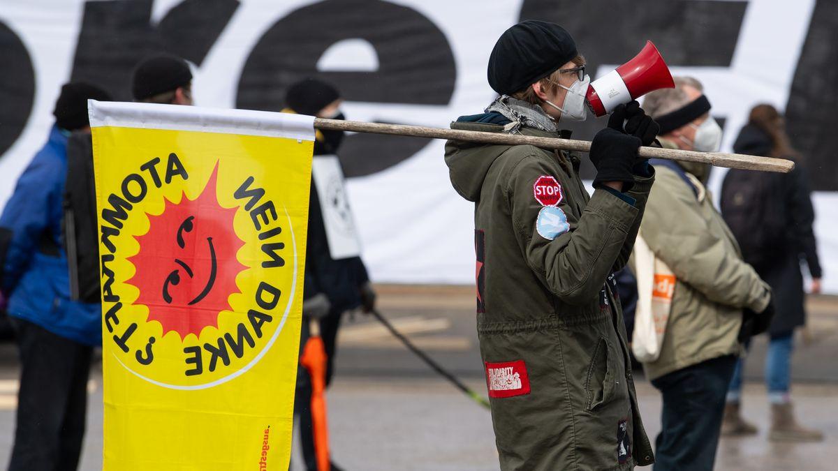 """Ein Demonstrant trägt eine gelbe Flagge mit der Aufschrit """"Atomkraft? Nein danke""""."""