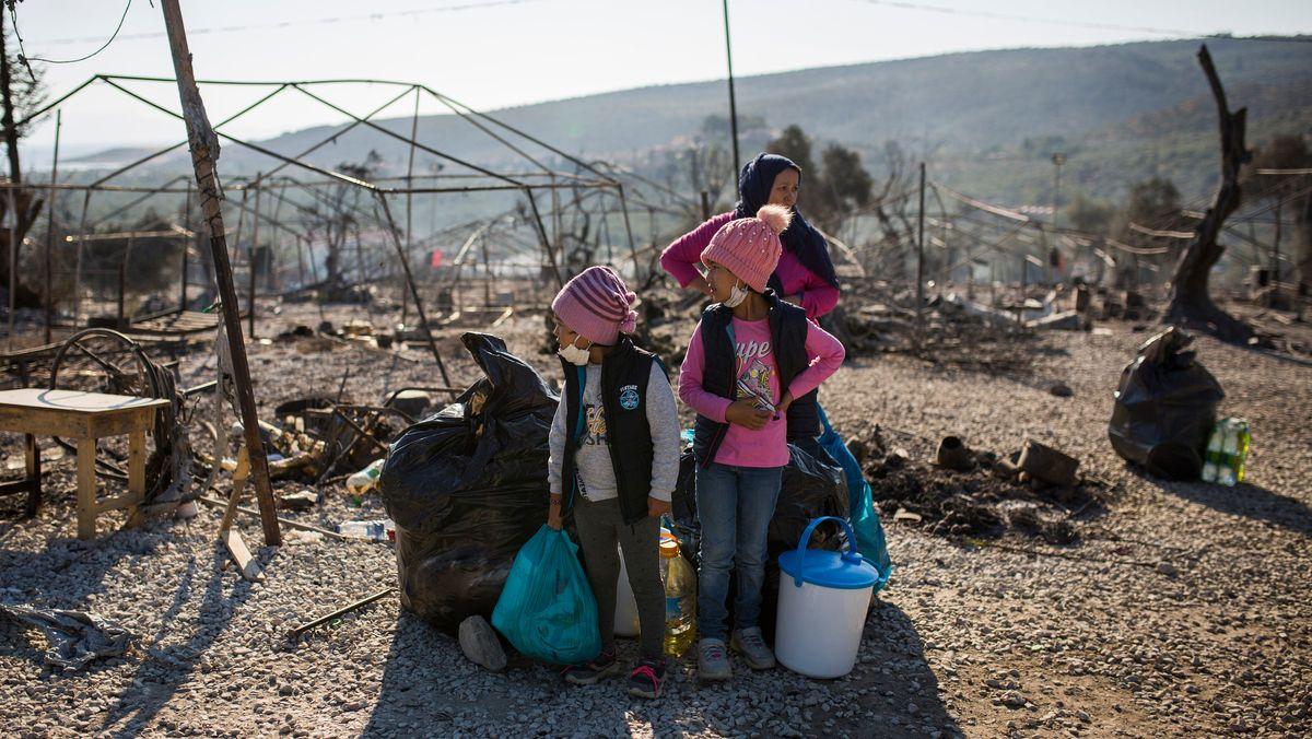 Eine Familie steht im ausgebrannten Flüchtlingslager Moria