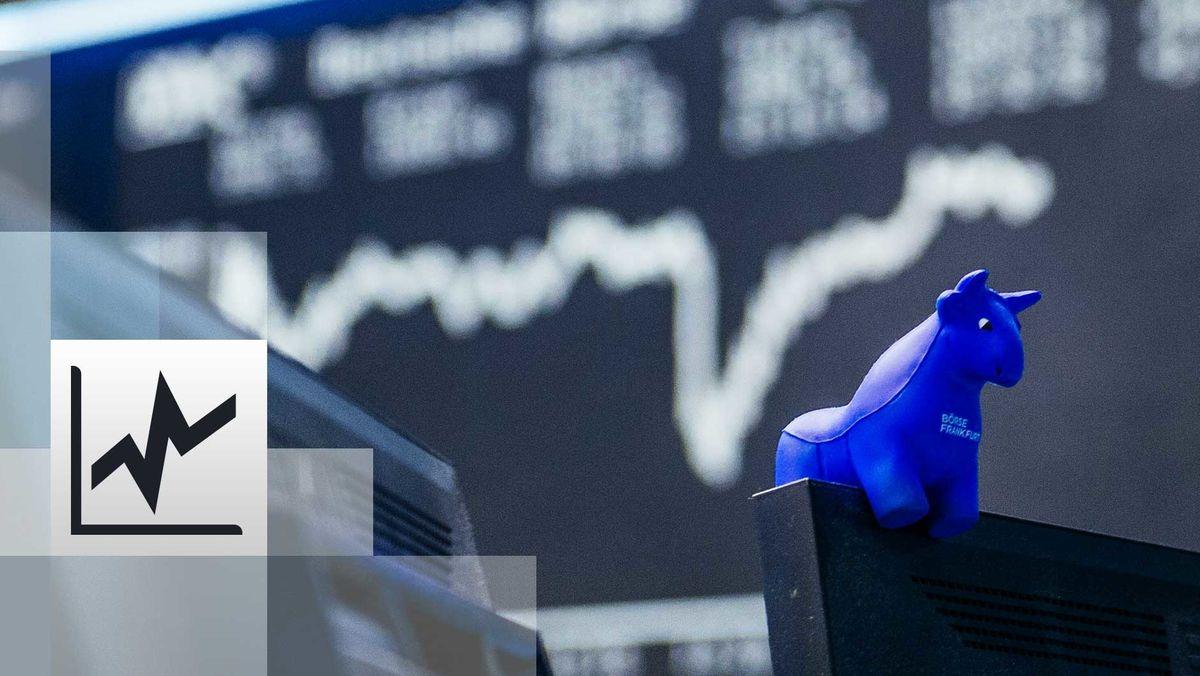 ein blauer Stier aus Gummi sitzt auf der oberen Kante eines Bildschirmes, im Hintergrund die Kurstafel der Börse