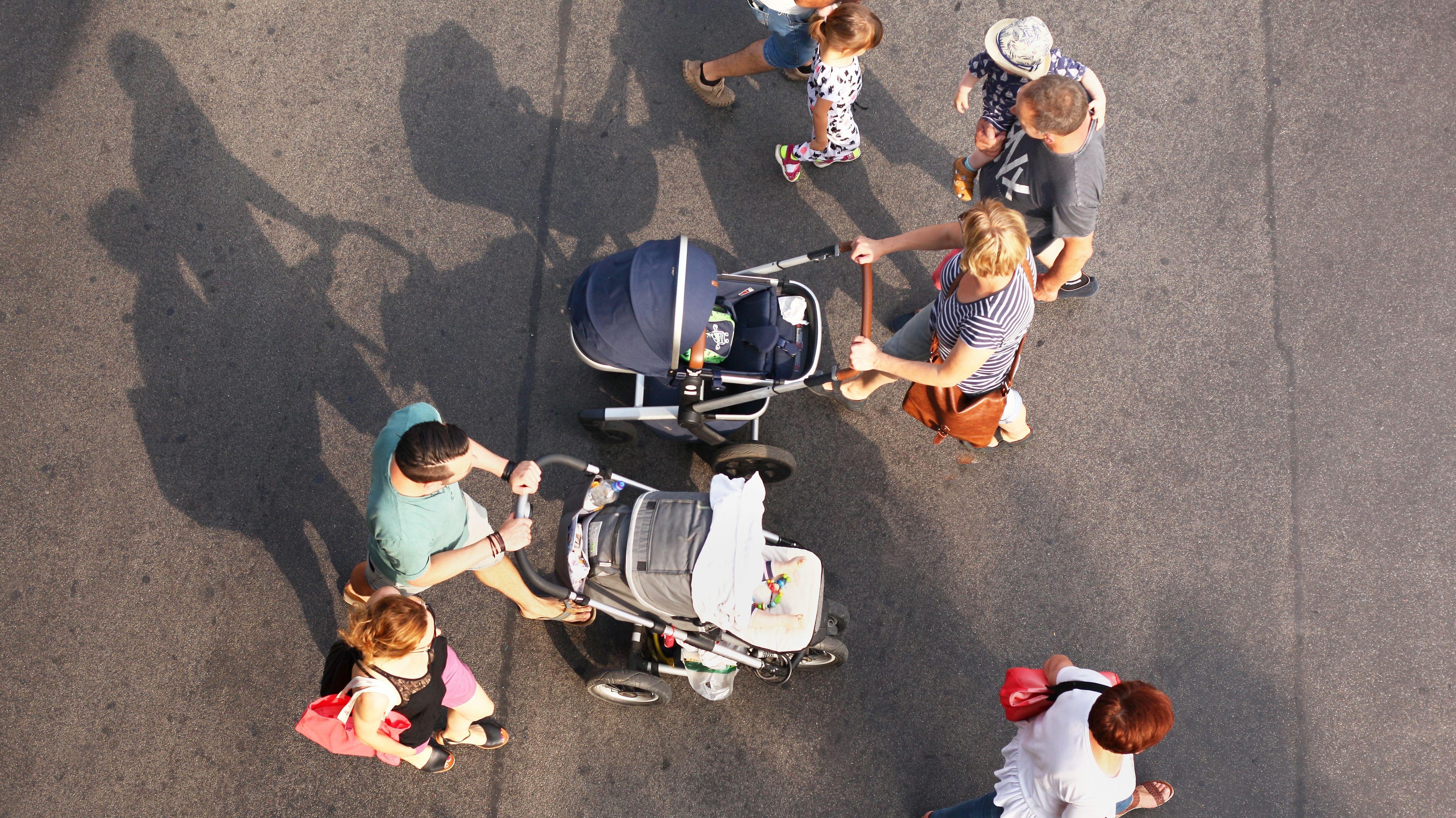Familien mit Kinderwägen gehen über die Straße