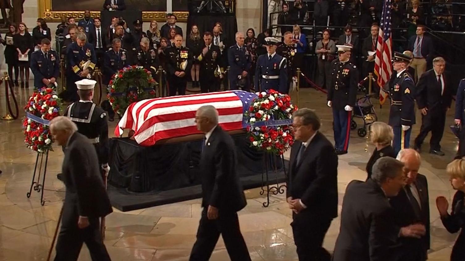 Sarg des verstorbenen ehemaligen US-Präsidenten George H. W. Bush mit der US-Flagge bedeckt wird auf einer Lafette hereingetragen.