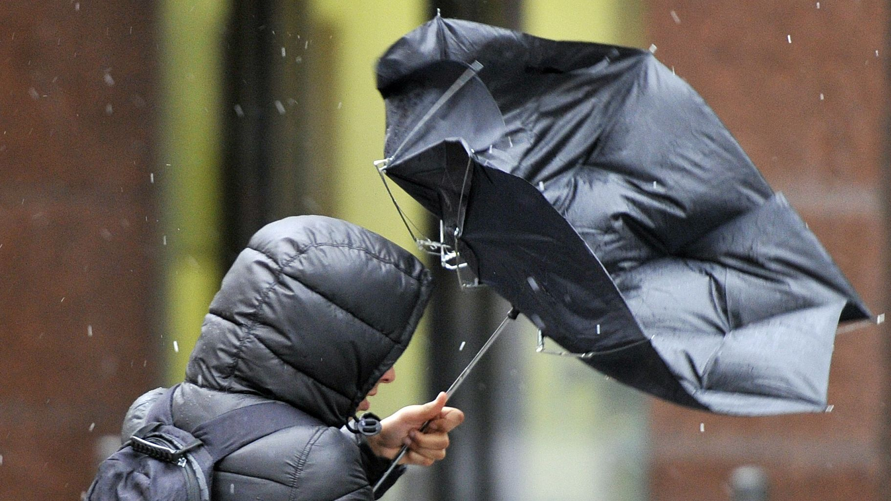 Der Regenschirm eines Mannes wird vom Wind deformiert.