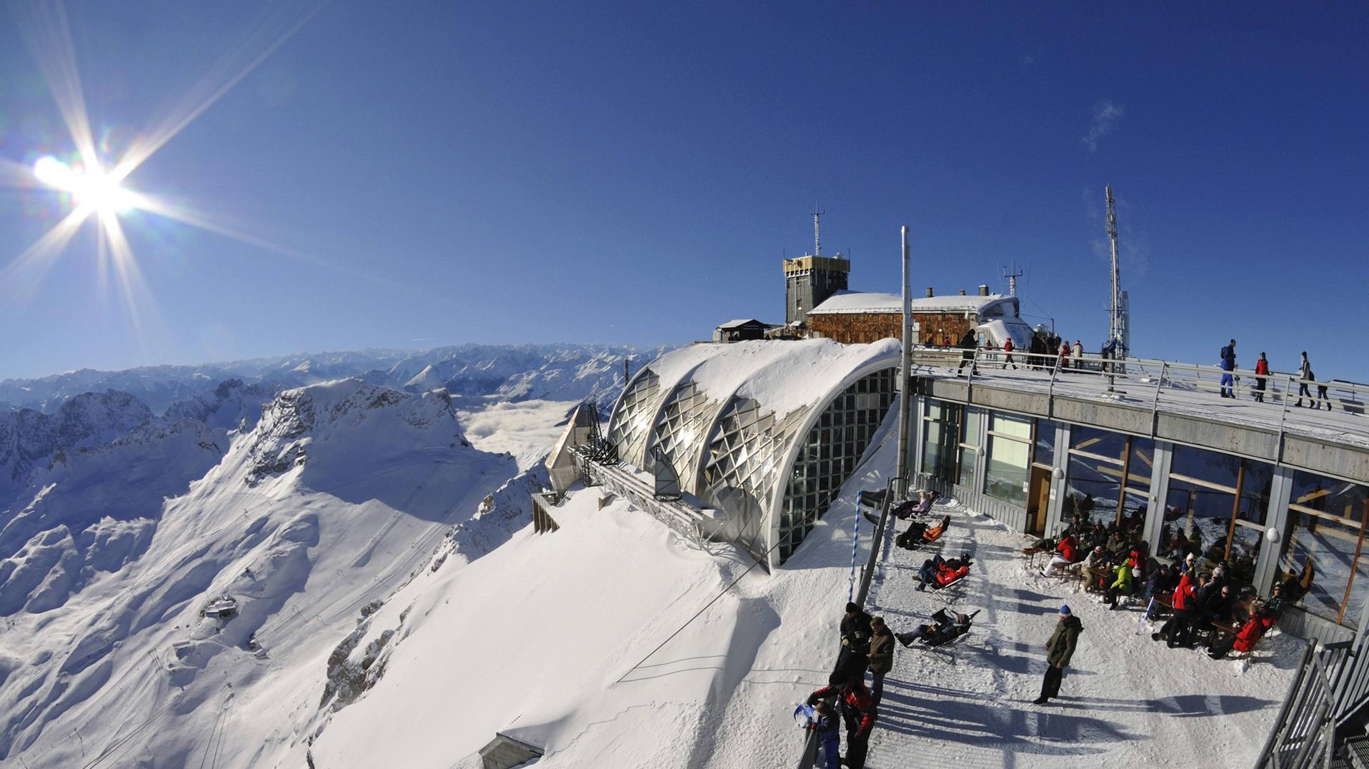 Menschen sonnen sich im Winter auf der Aussichtsplattform der Zuspitze