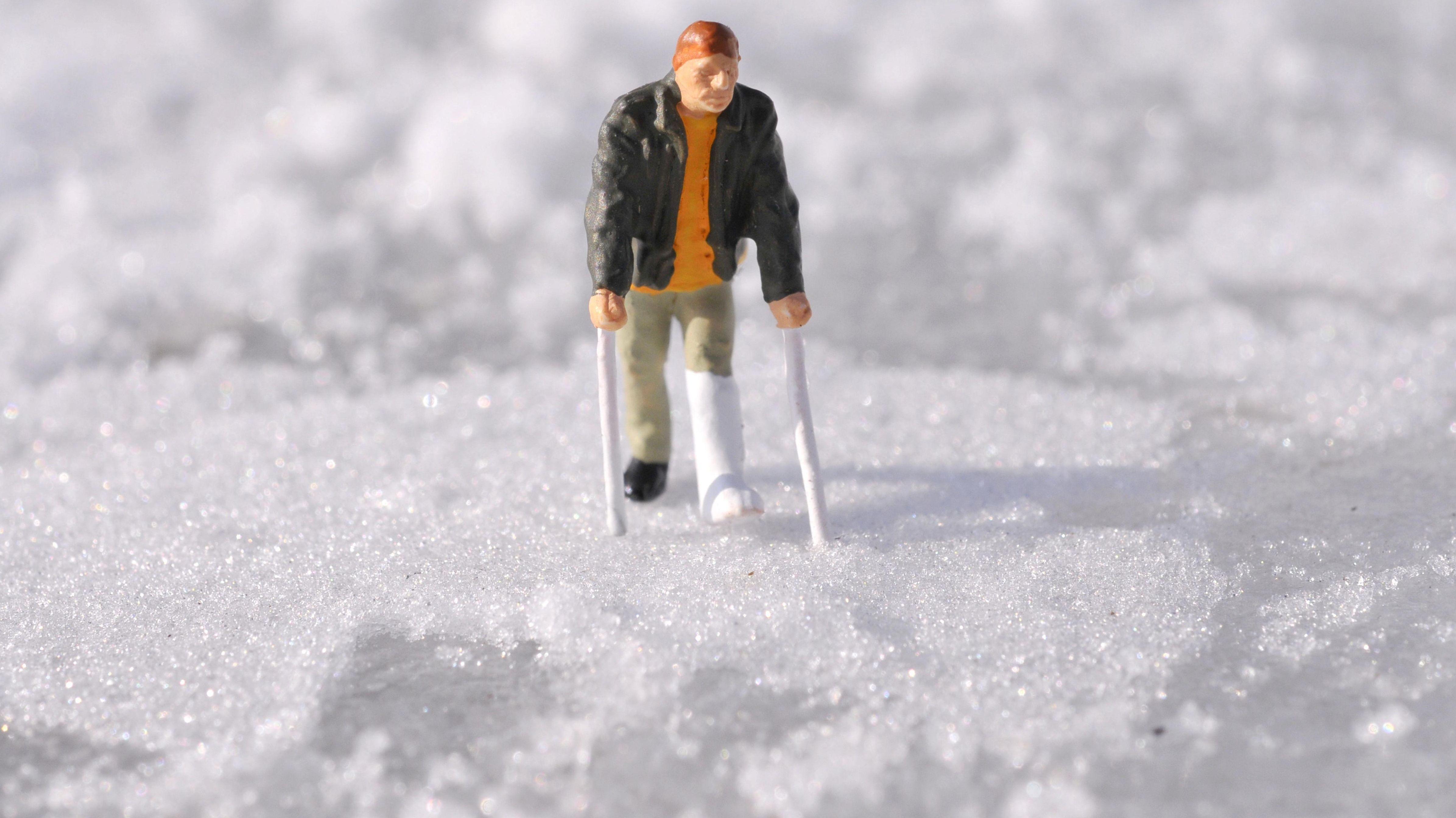 Kleine Spielfigur mit eingegipsten Bein im Schnee