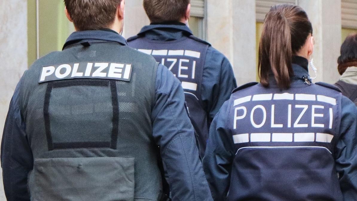 Drei Polizisten von hinten in dunkelblauer Unform mit weißer Polizei Aufschrift auf dem Rücken.