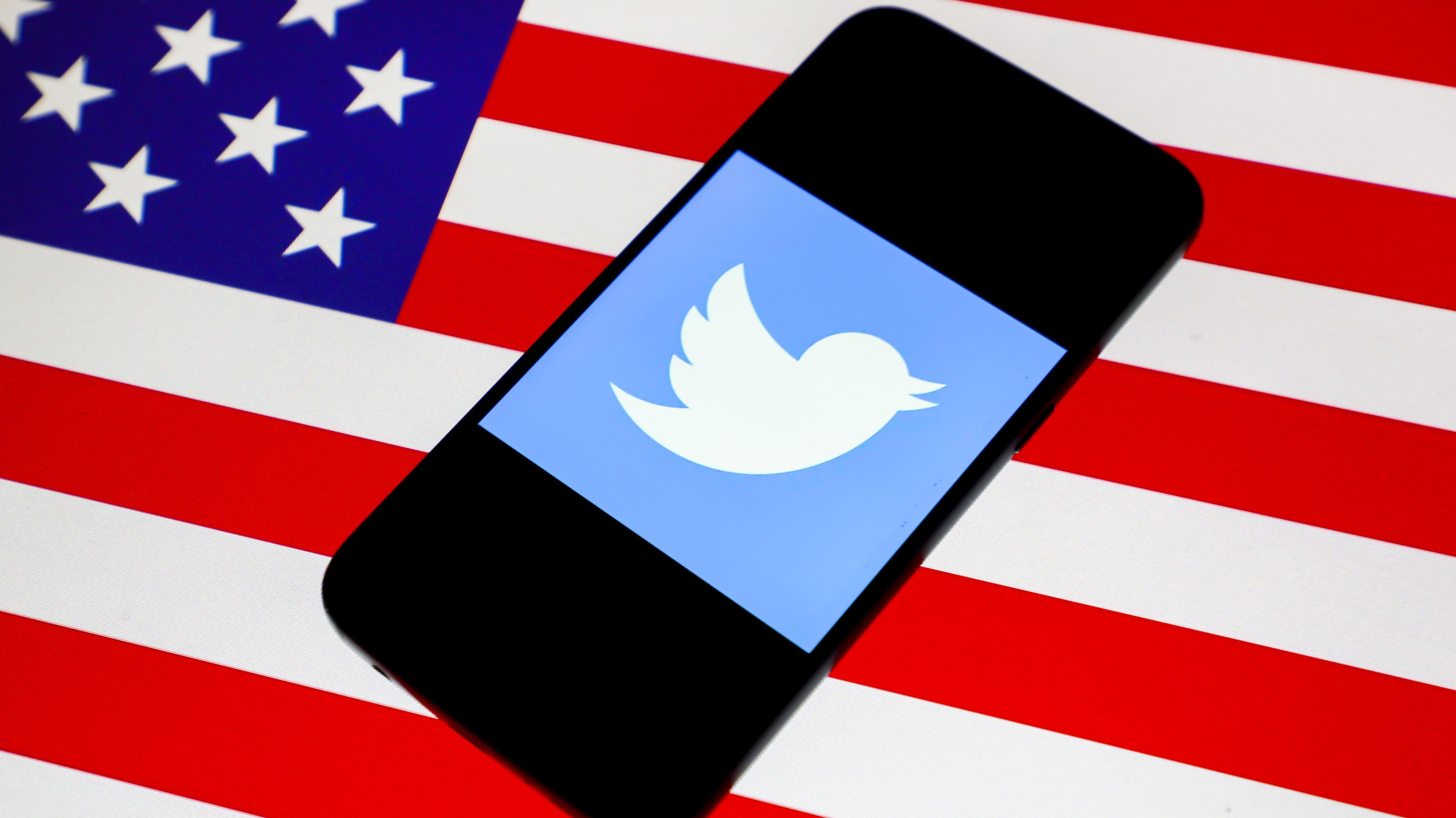 Smartphone mit Twitter-Logo liegt auf US-Flagge