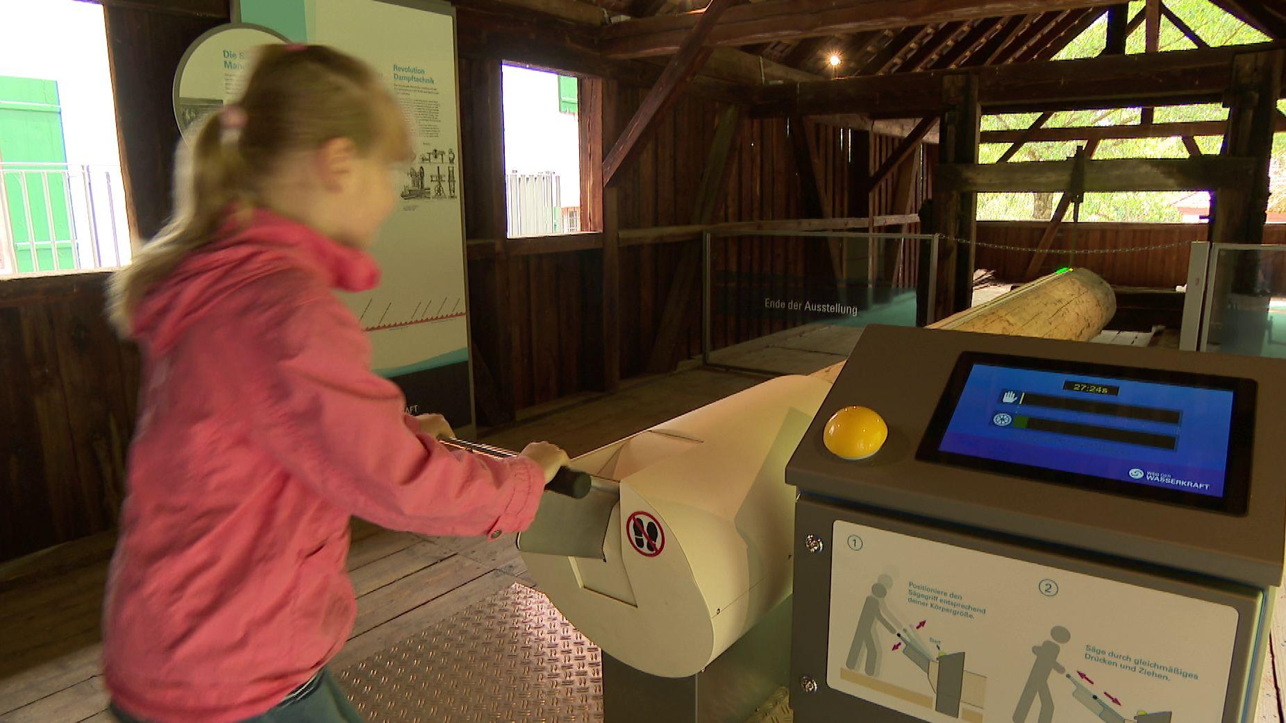 """Eine Besucherin des Erlebnispfads erlebt an einer Mitmach-Station den  """"Weg der Wasserkraft""""."""