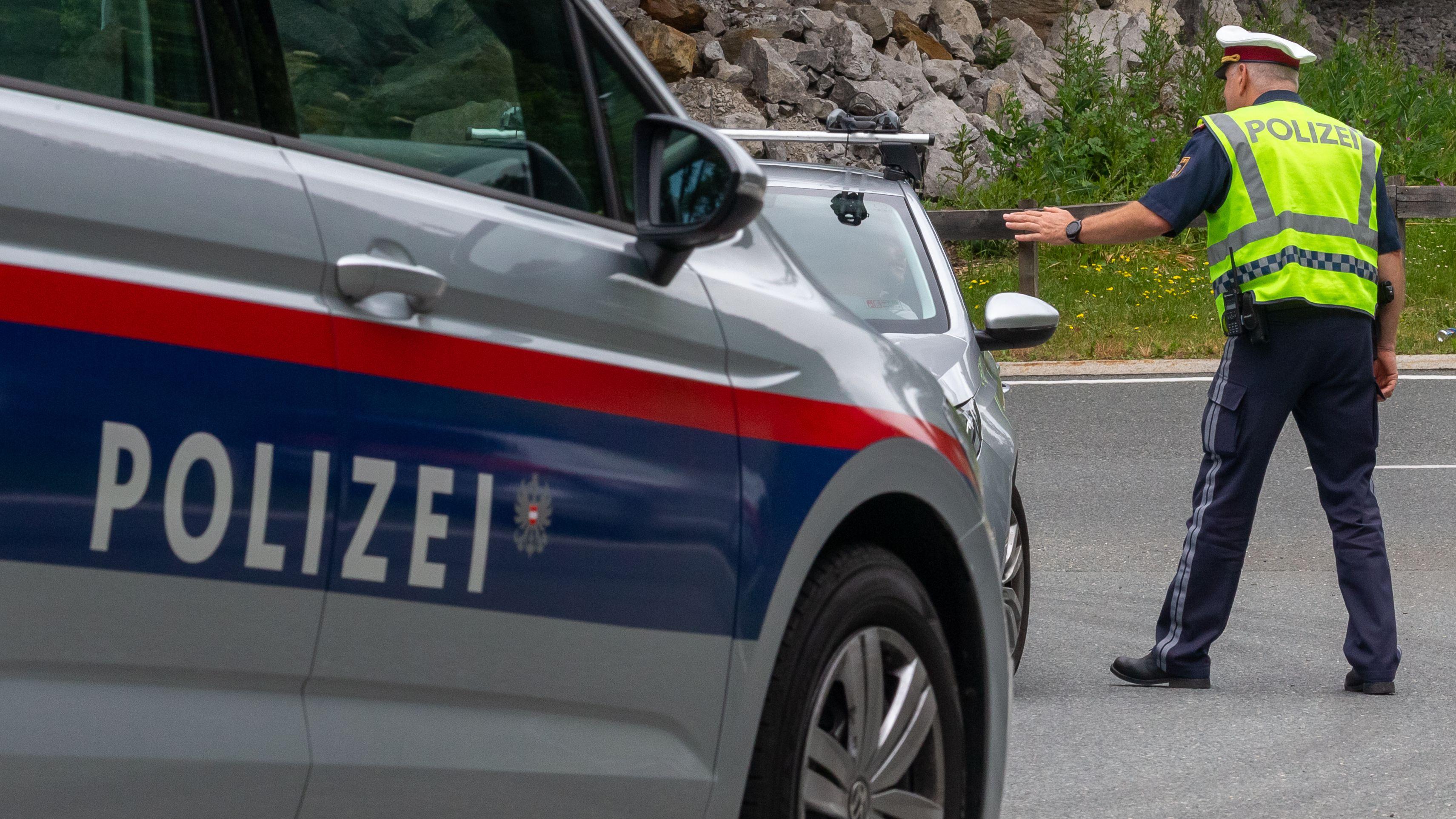 Streifenwagen in Tirol – im Hintergrund kontrolliert ein Polizist einen Pkw