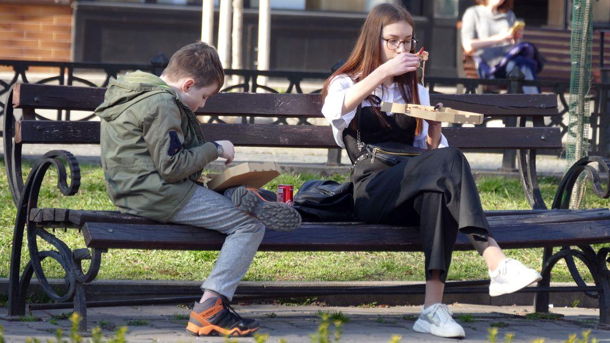Junge und Mädchen essen Pizza auf einer Parkbank