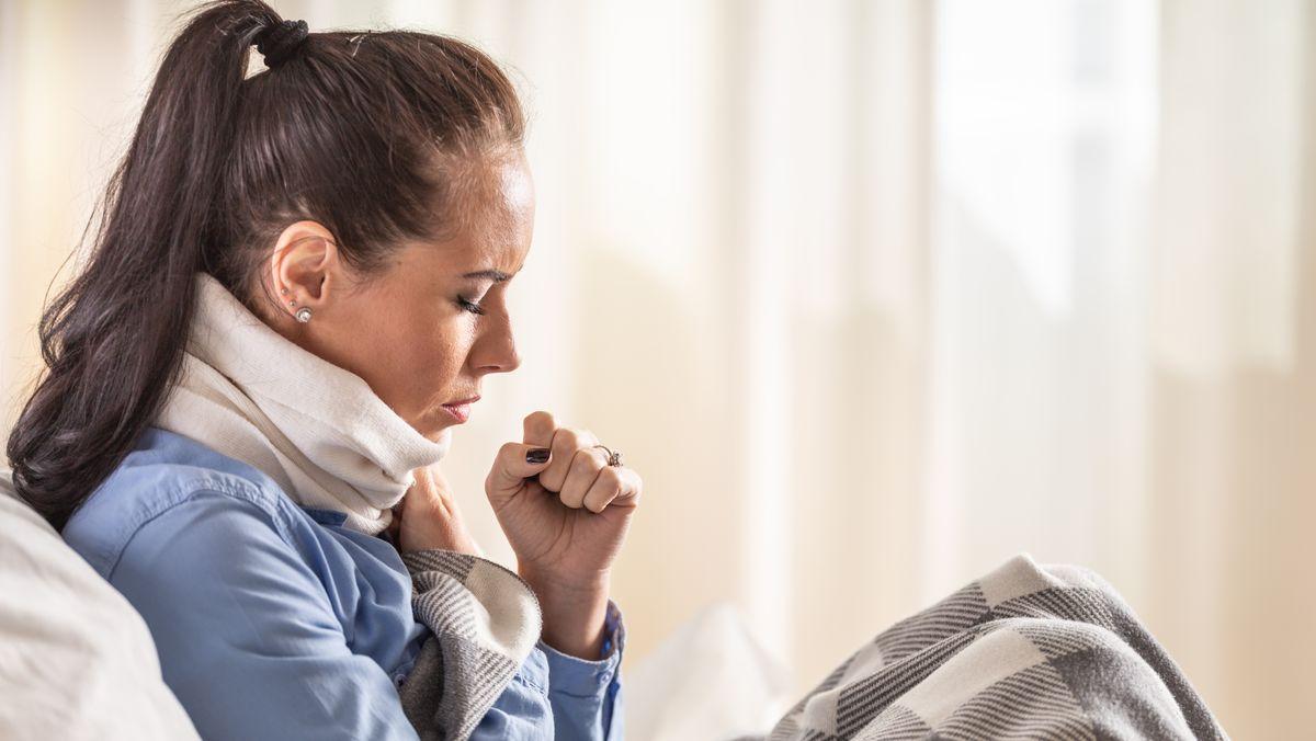 Frau sitzt krank auf dem Sofa.