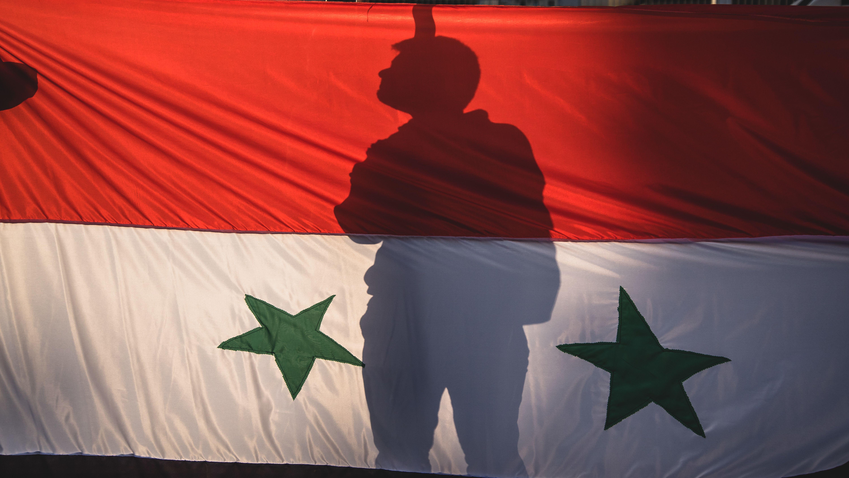 Schattenriss eines Mannes hinter einer Syrischen Fahne