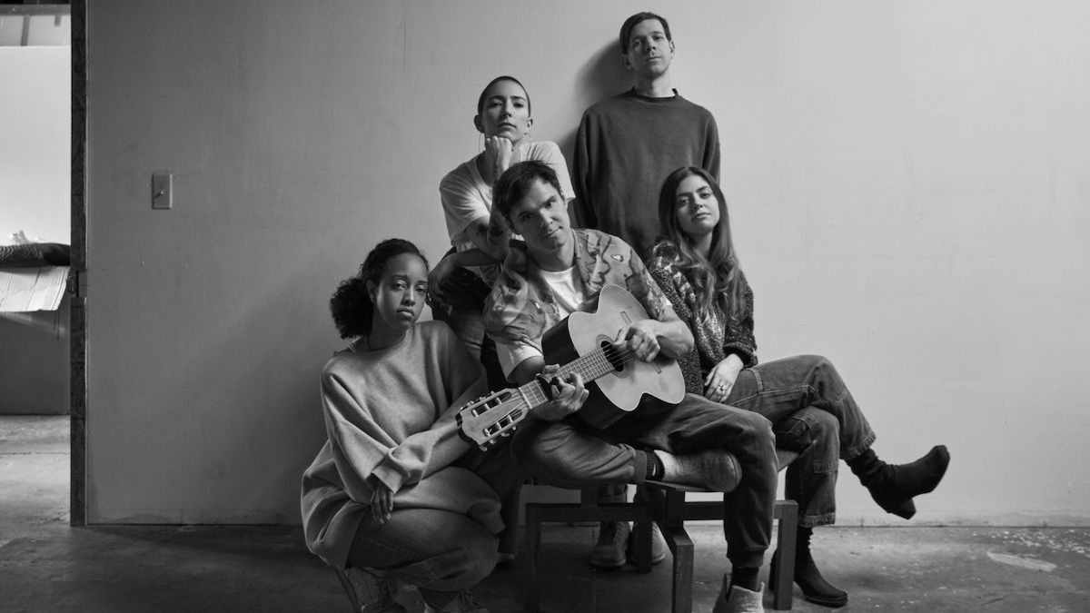 Songschreiber David Longstreth sitzt mit Akustik-Gitarre in der Mitte, umgeben von seinen Kolleginnen.