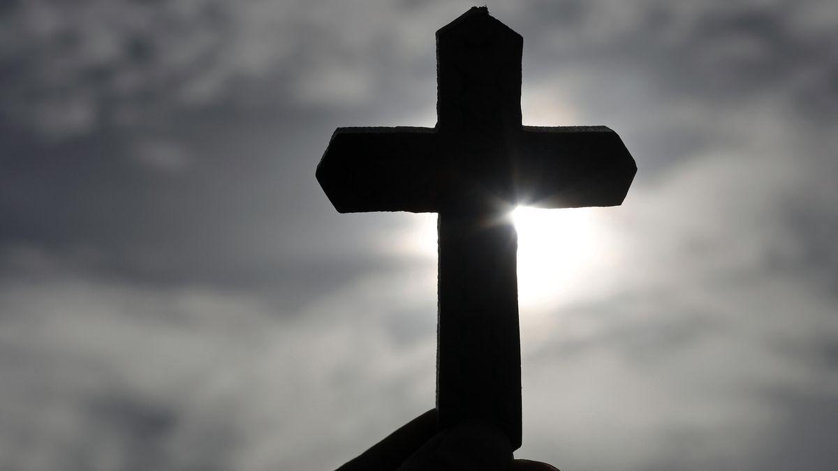 Ein christliches Holzkreuz vor einem dunklen Himmel