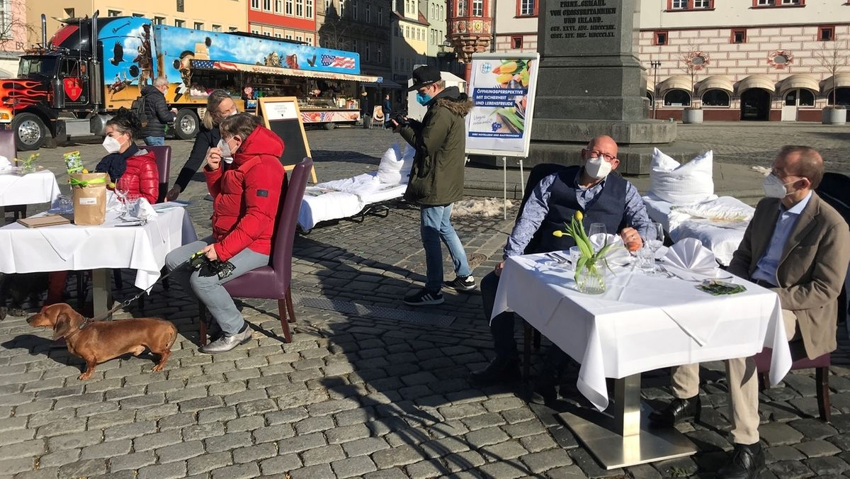 Eingedeckte Tische und gemachte Betten stehen in Coburg auf dem Marktplatz. An den Tischen sitzen Personen.