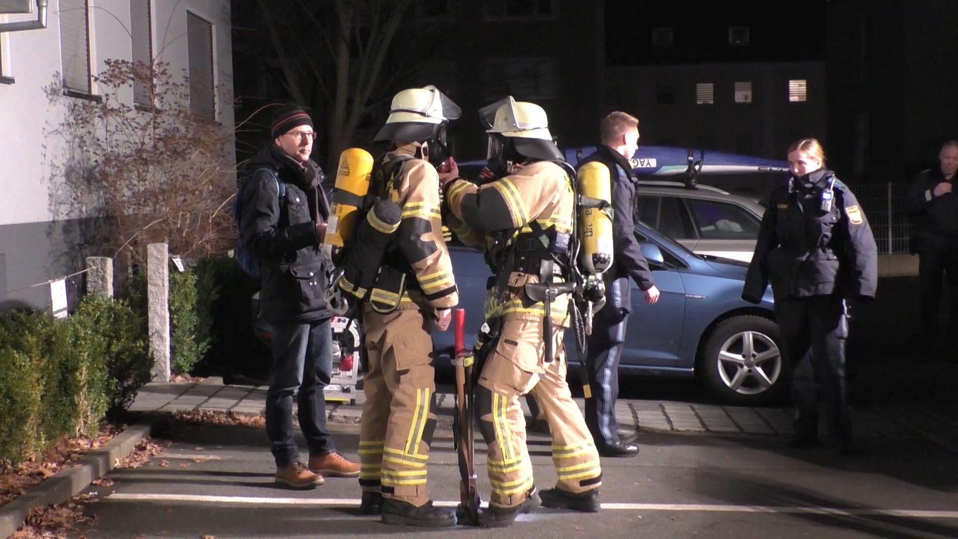 Feuerwehrleute stehen nachts auf einer Straße