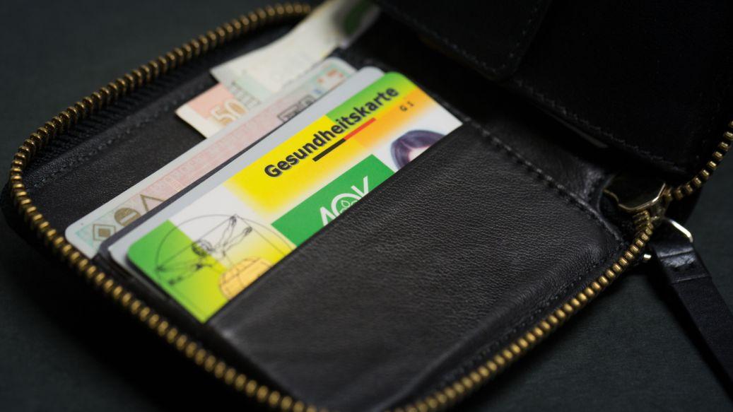 Brieftasche mit Krankenversichertenkarte und Geldscheinen