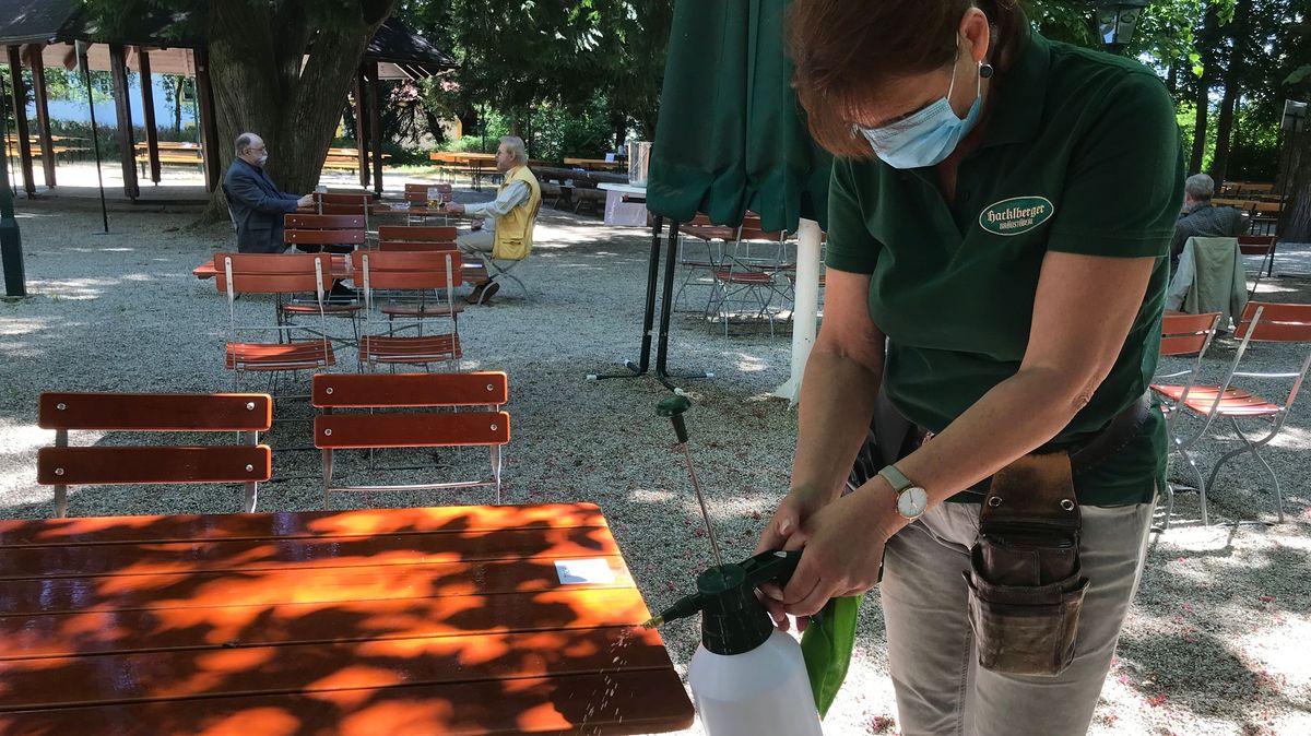 Eine Angestellte desinfiziert einen Tisch im Biergarten