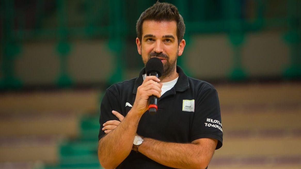 """Der sportliche Leiter von """"medi bayreuth"""", Matthais Hauer, im schwarzen Polohemd spricht in ein Mikrophon."""