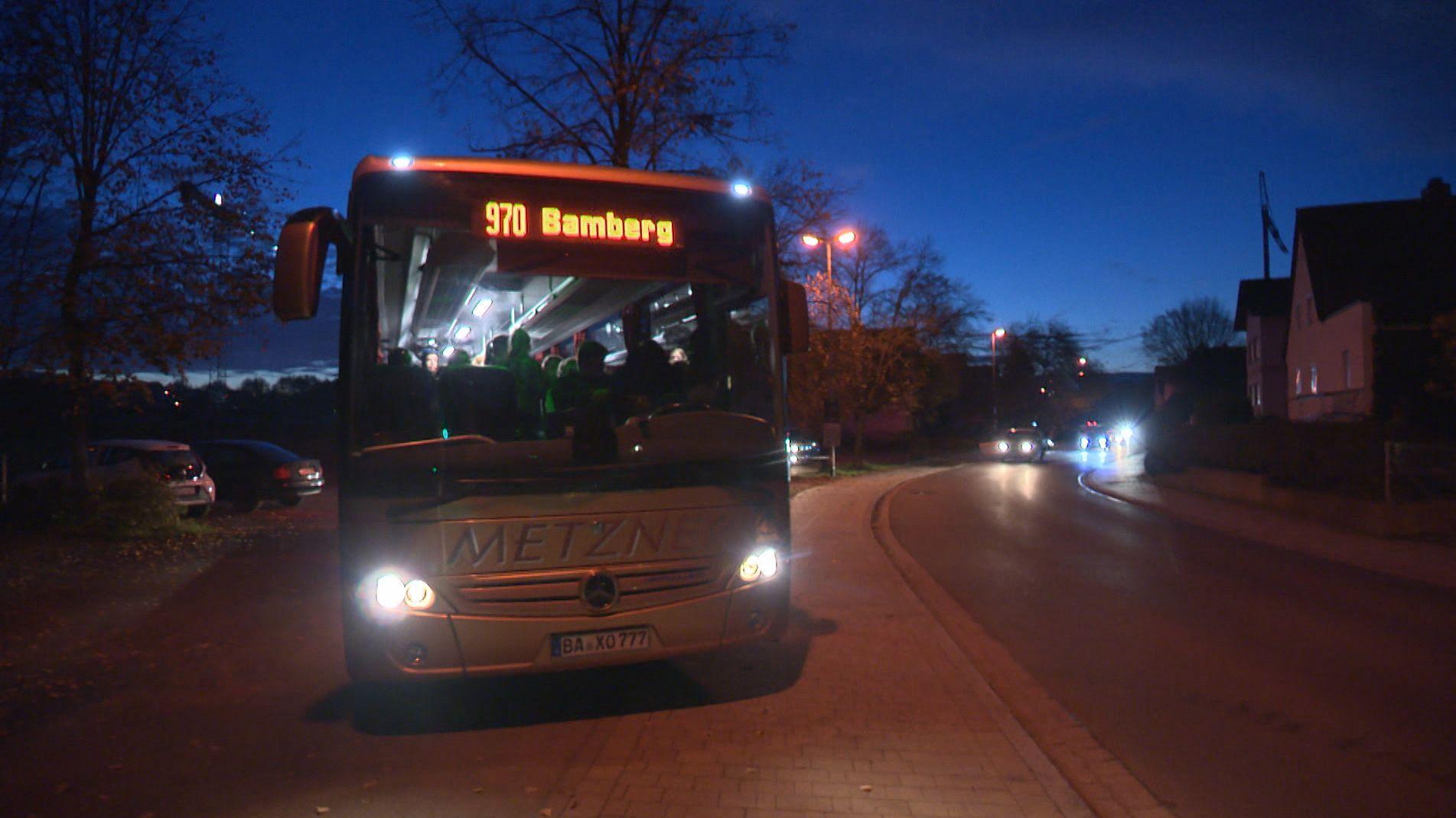 Ein vollbepackter Schulbus steht im Morgengrauen an einer Bushaltestelle