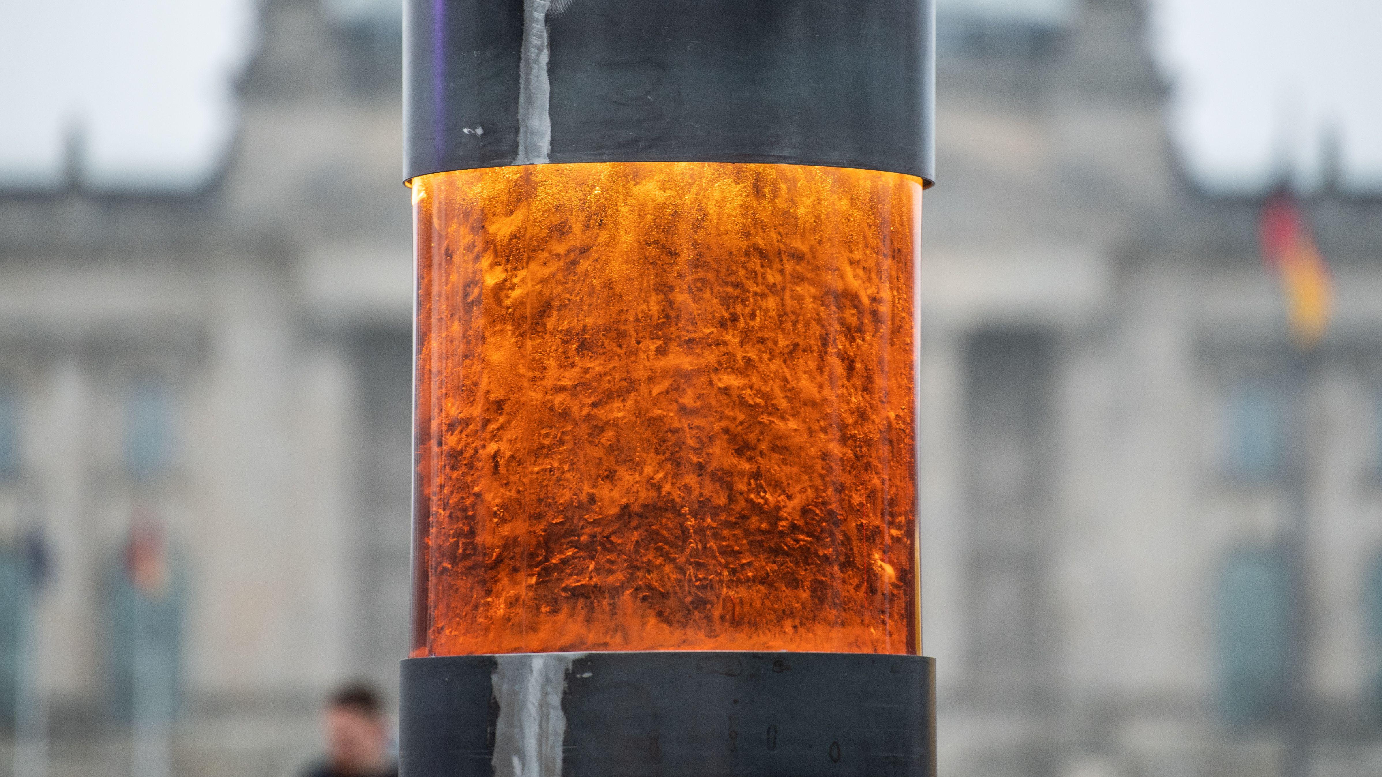 Eine Nahaufnahme der Gedenksäule, angeblich mit Asche von NS-Opfern, dahinter unscharf der Reichstag