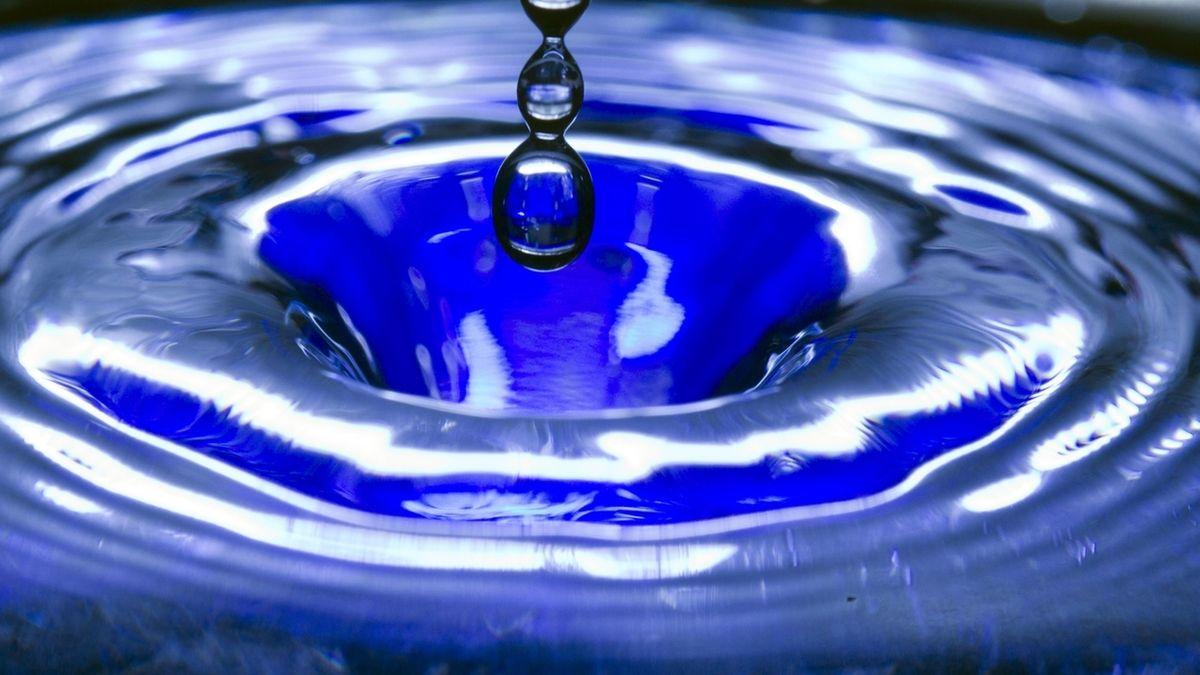Ein Wassertropfen fällt in eine blaue Wasserschüssel (Symbolbild)