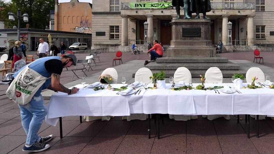 Ein gedeckter Tisch aus einem Weimarer Restaurant steht auf dem Theaterplatz vor dem Goethe-Schiller-Denkmal.