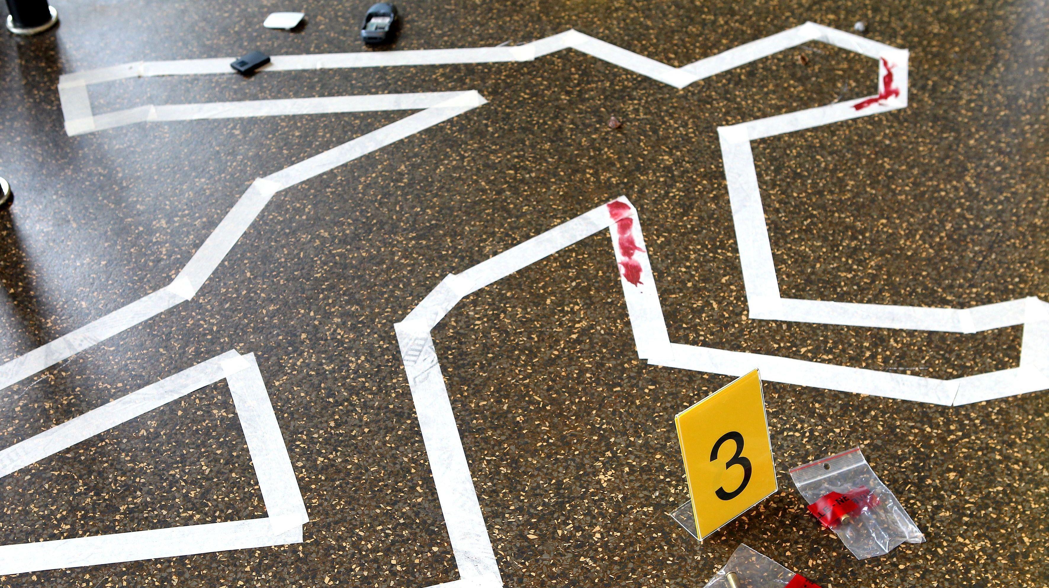 Mit weißer Kreide auf den Boden gezeichneter Umriss einer Leiche