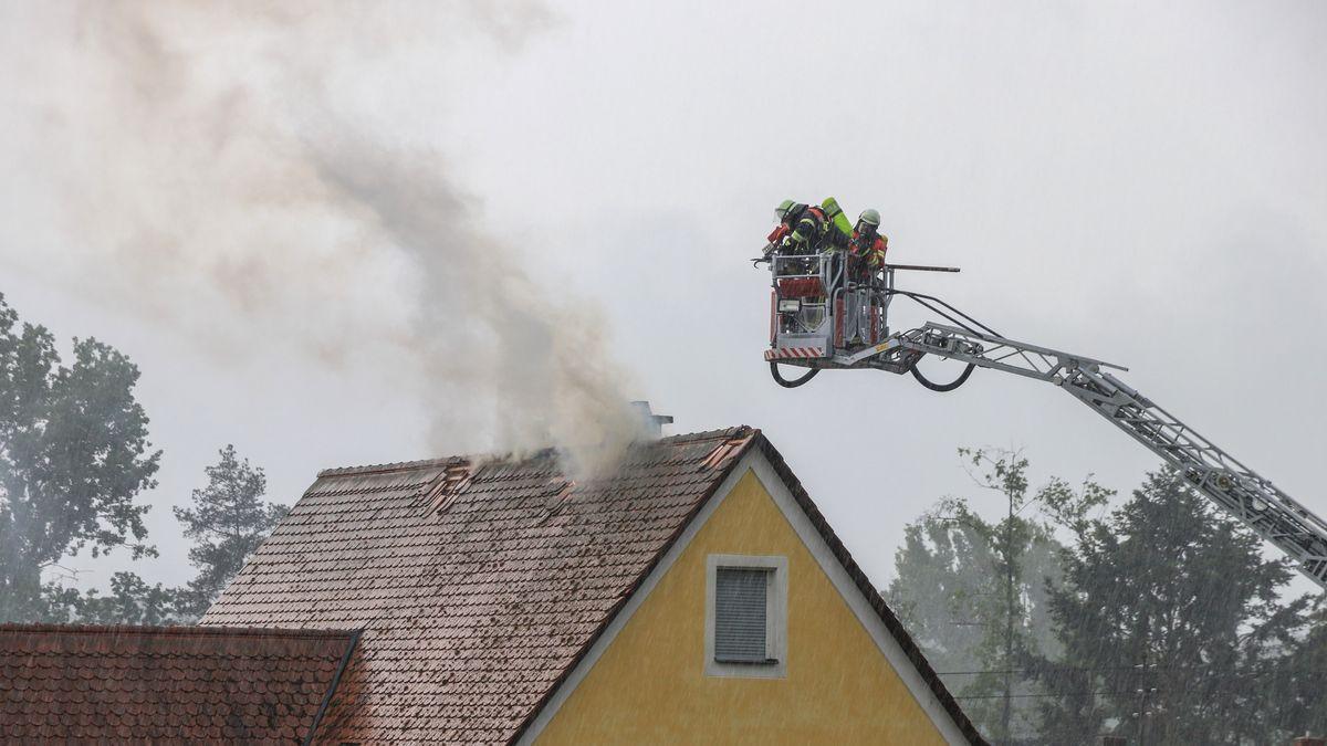 Feuerwehrleute löschen mit Drehleiter einen Dachstuhlbrand