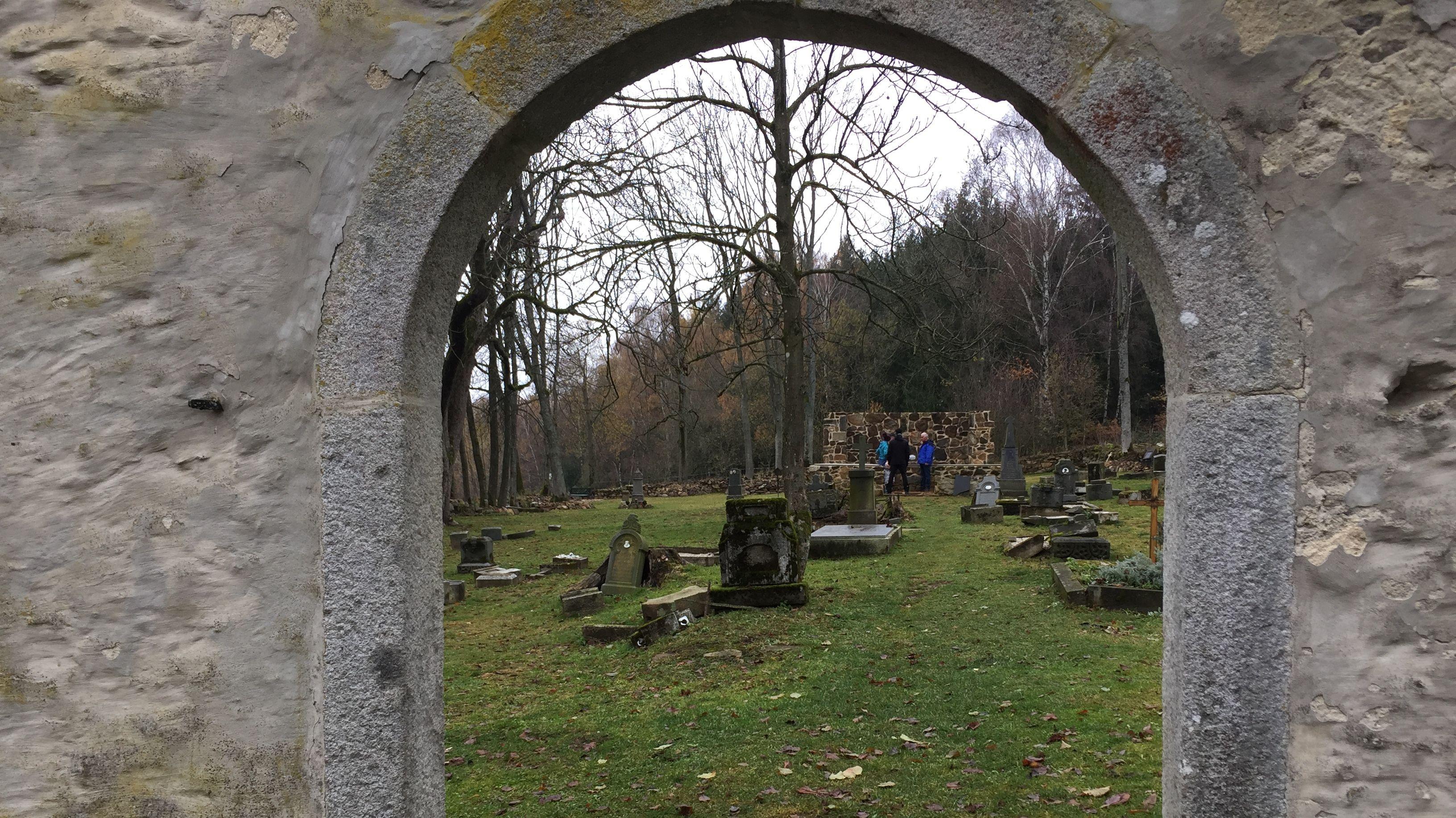 Blick durch einen Rundbogen auf den alten Friedhof von Grafenried.