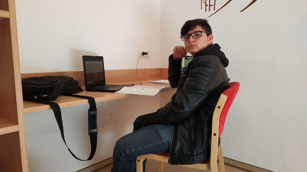 Ivo sitzt am Schreibtisch in einem Zimmer der Jugendbildungsstätte Volkersberg.