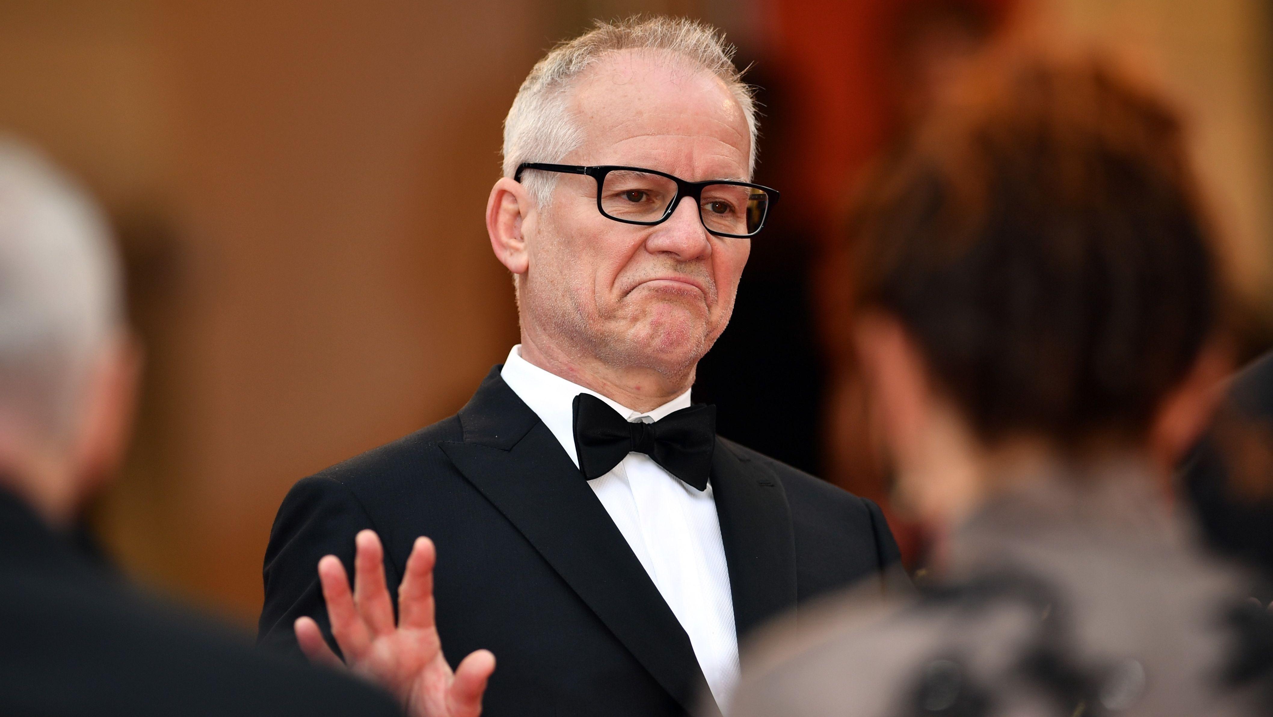 Festivalleiter Thierry Frémaux trägt einen Smoking und macht eine abweisende Geste