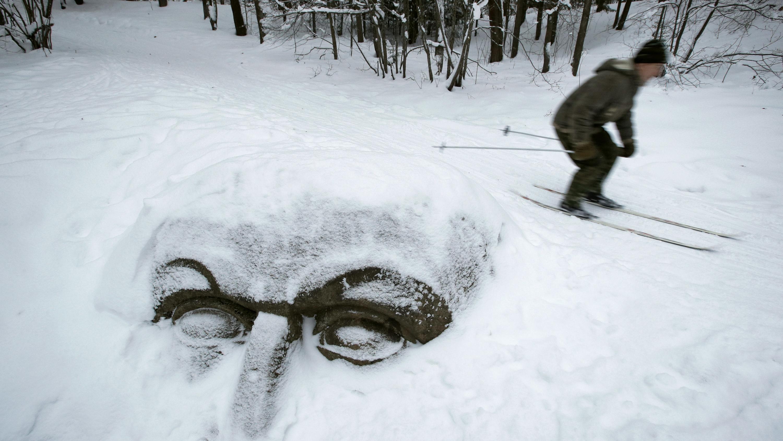 Russland, St.Petersburg: Ein Mann auf Skiern fährt an einem schneebedeckten, riesigen, aus Stein gehauen Kopf vorbei