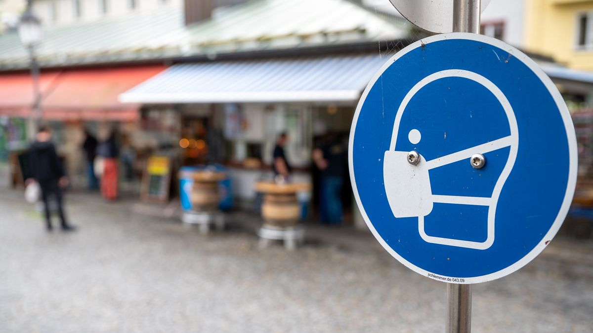 Bayern, München: Ein Schild fordert am Viktualienmarkt in der Innenstadt zum Tragen einer Mund und Nasen Bedeckung auf.