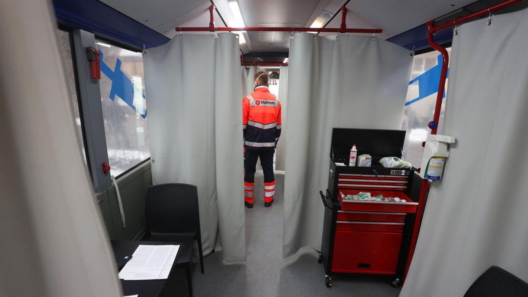 Ein Mitarbeiter der Hilfsorganisation Malteser steht am städtischen Impfzentrum in einem Impfbus.