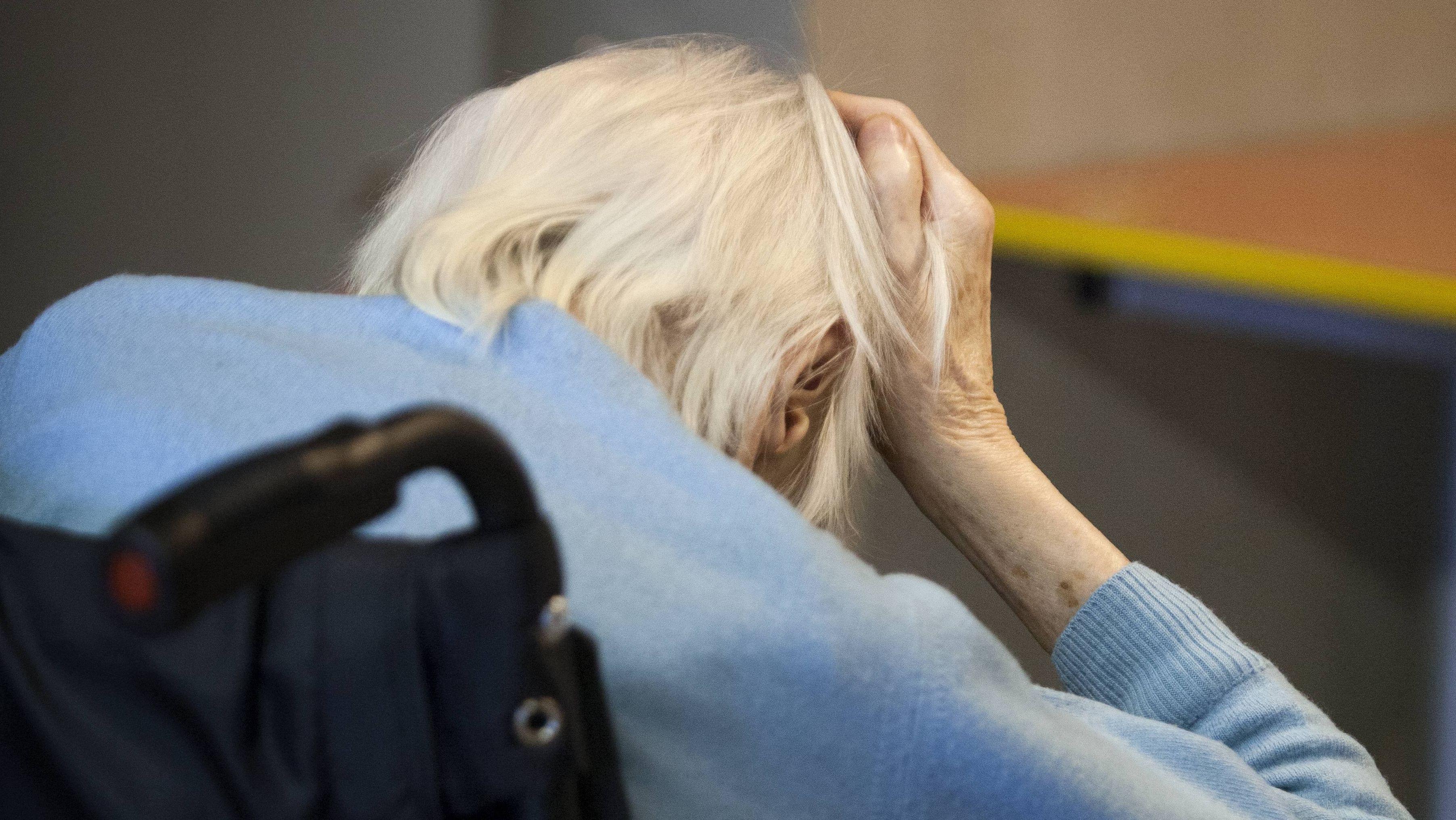 Seniorin im Rollstuhl, das Gesicht in die Hände gestützt (Symbolbild)