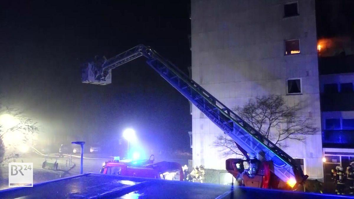 Feuerwehrleute in einer Drehleiter an einem Hochaus.