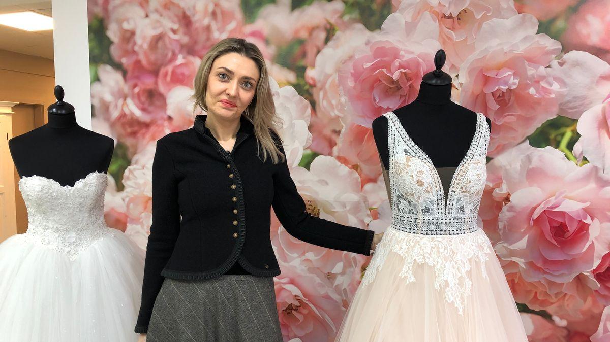 Inhaberin des Brautmodengeschäftes Christina Thumbach steht zwischen zwei weißen Brautkleidern, von Puppen getragen