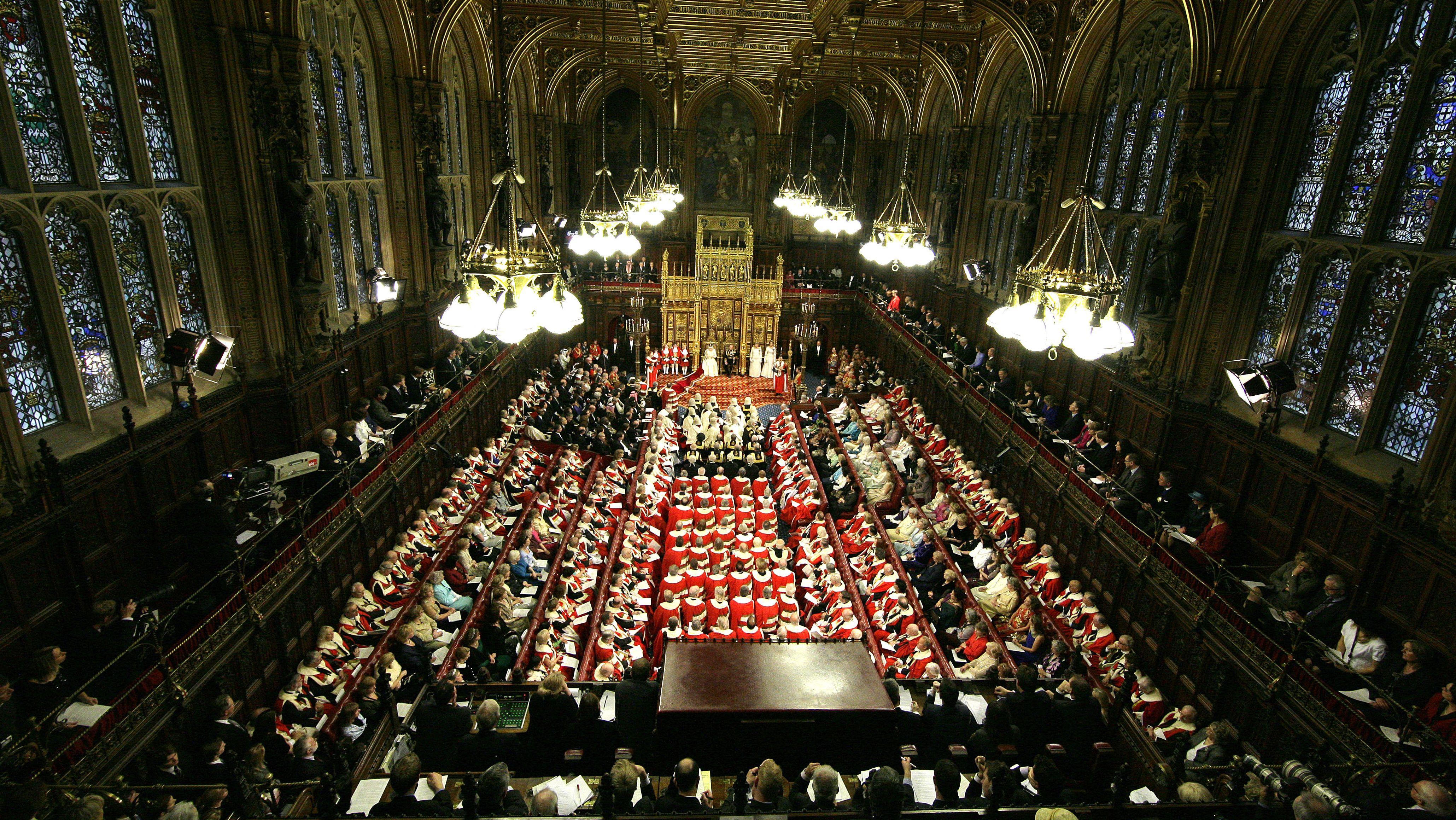 Das britischen Parlaments im House of Lords aus der Vogelperspektive: Ein großer, gothischer Saal mit hohen Bogenfenstern. Mehrere Sitzreihen an den beiden Fensterseiten und an der Hinterseite. In der Mitte Stehplätze mit den den einheitlich in rot gekleideten Lords. An der Stirnseite der Thron der Queen.