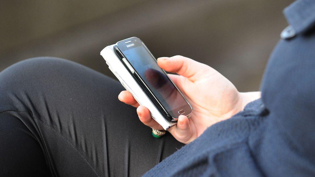 Mann schaut in sein Smartphone (Symbolbild)