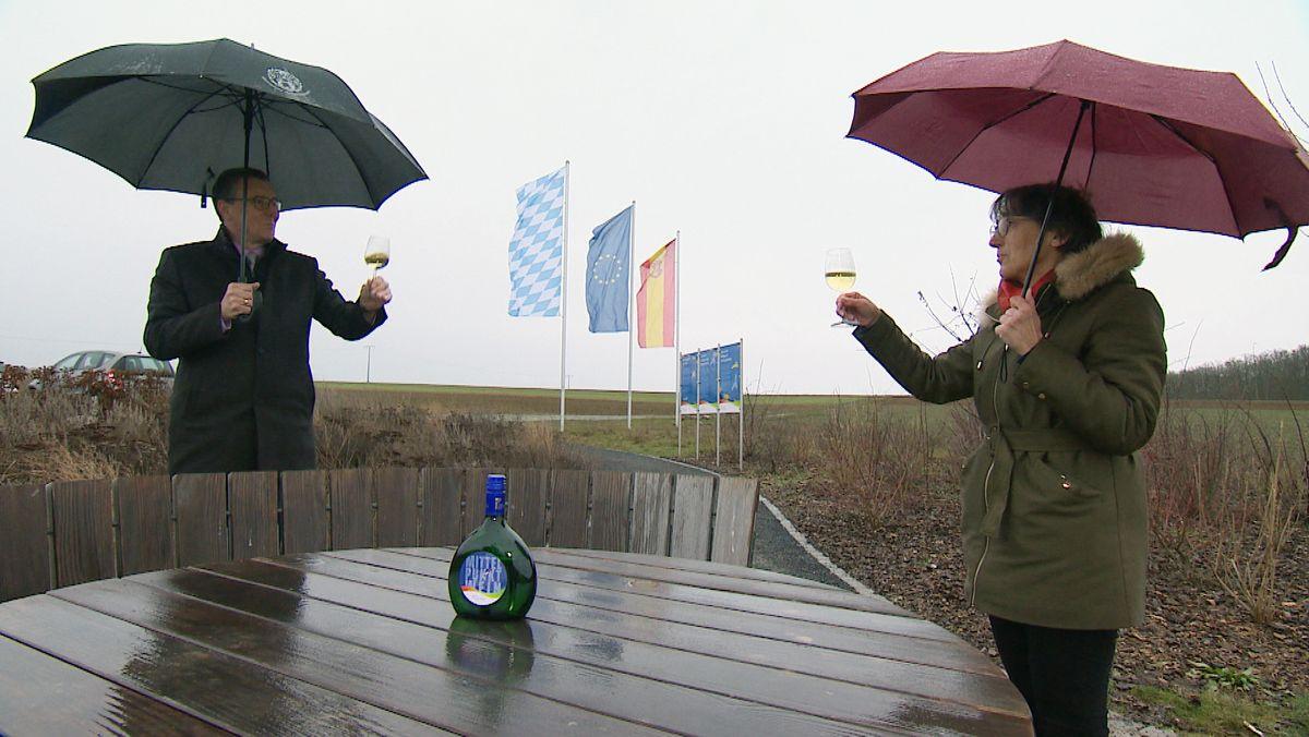Veitshöchheims Bürgermeister Jürgen Götz und Petra Reichert-Südbeck von der Tourist-Information prosten sich am Mittelpunkt der EU mit Wein zu.