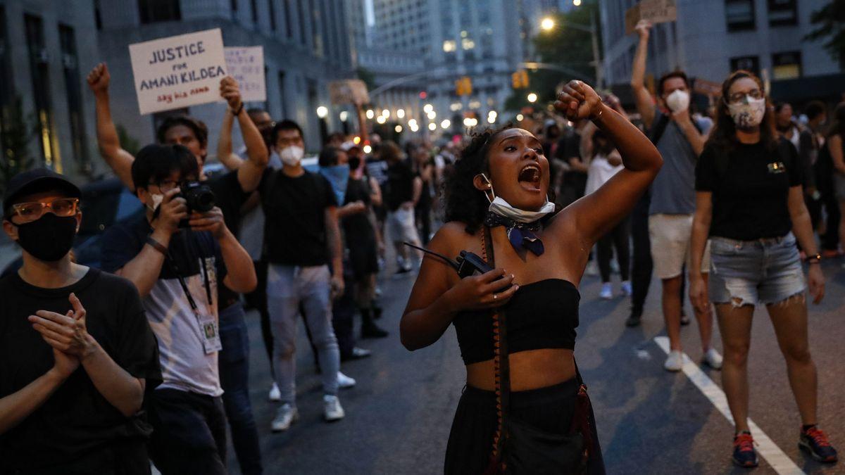 Auf einer New Yorker Straße hebt eine junge Frau die Faust zum Himmel. Um sie herum stehen andere Demonstranten mit Schildern.
