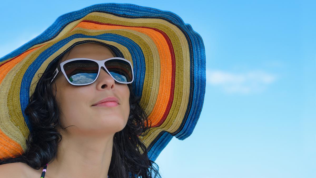 Frau mit Sonnenhut und Sonnenbrille vor blauem Himmel